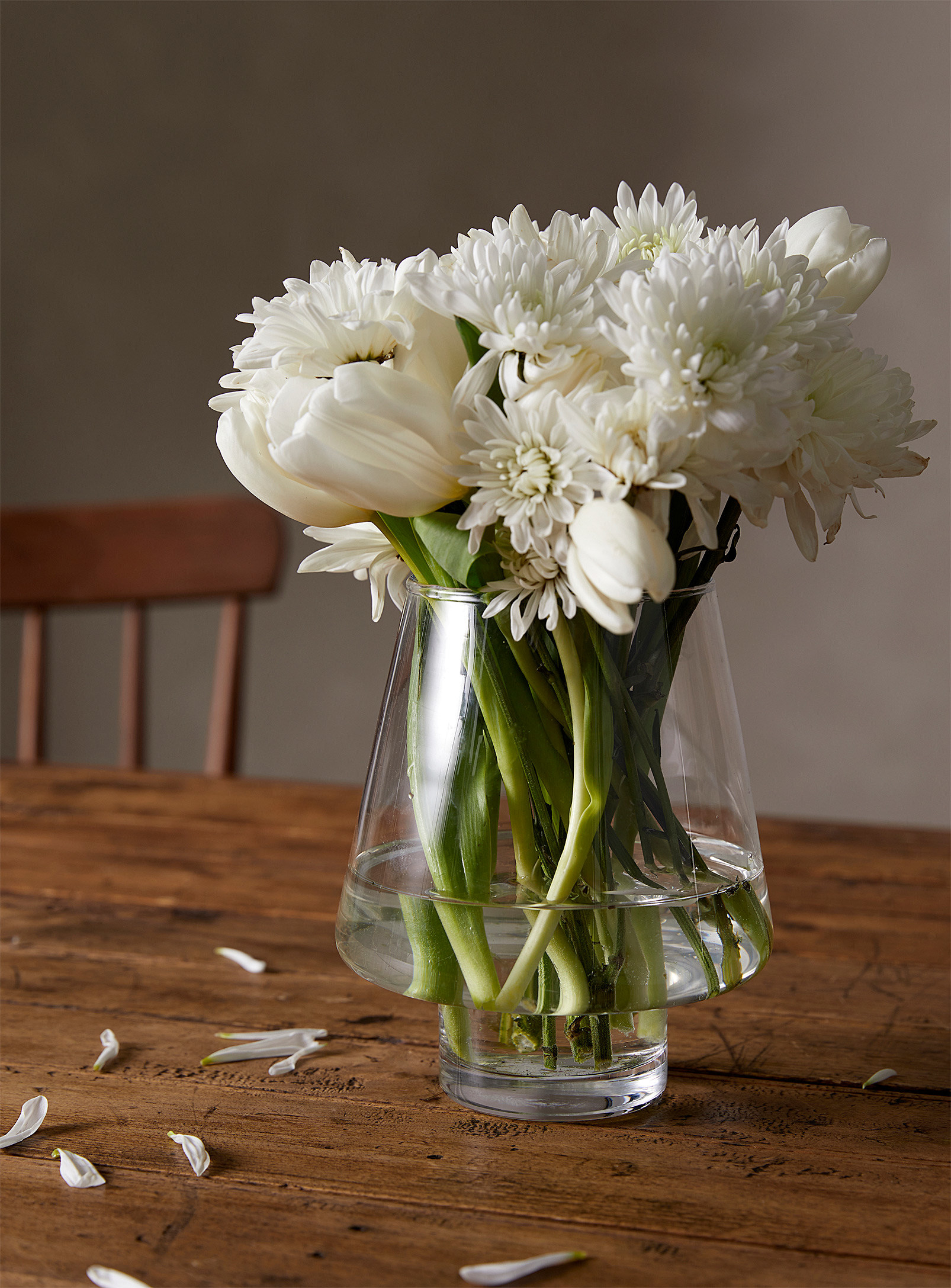 A tapered crystal vase filled with fresh cut flowers
