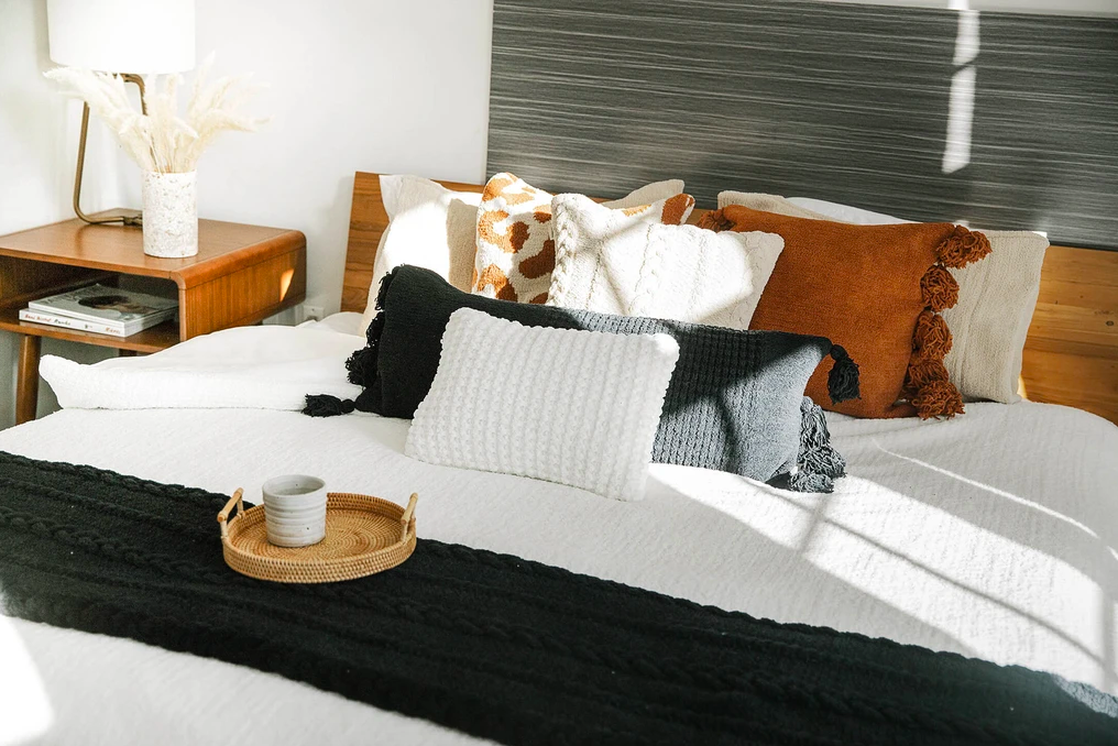 Bed with throw blanket and several decorative pillows in different shapes and styles