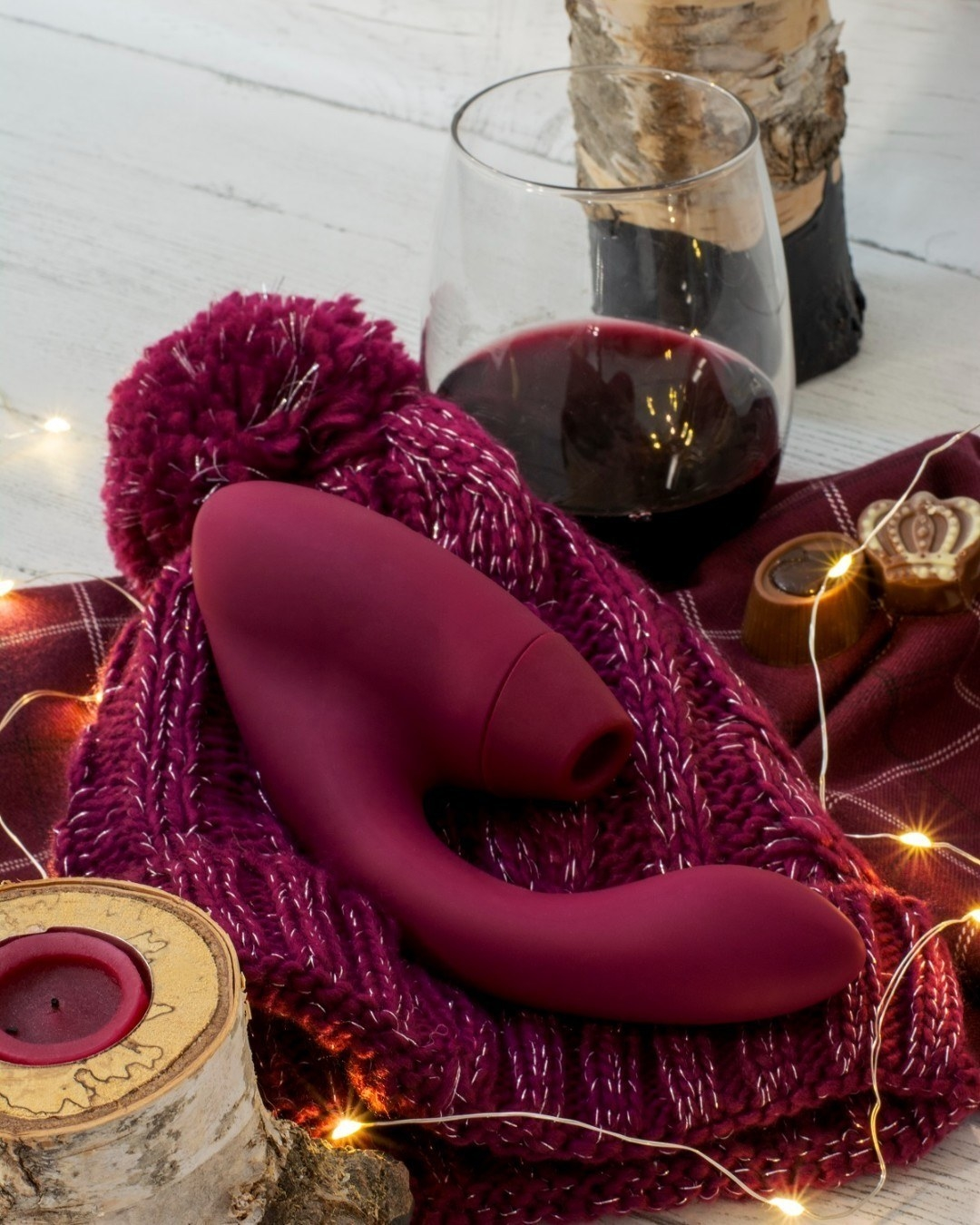 the womanizer duo atop a burgundy knit beanie hat surrounded by twinkle lights and a glass of red wine