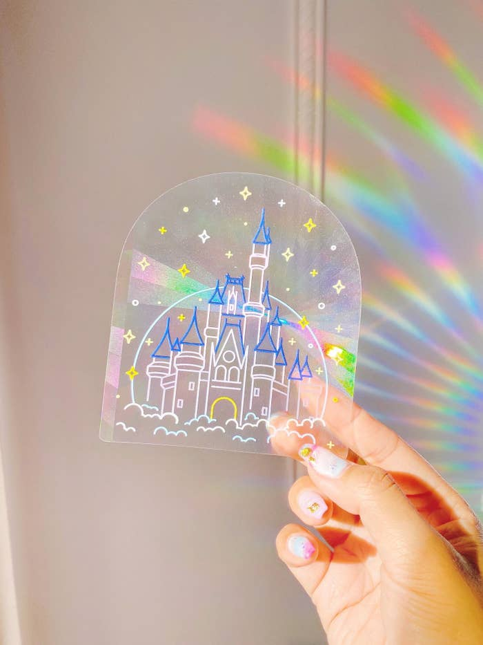 a model holding up a castle-shaped sun catcher with rainbows behind it
