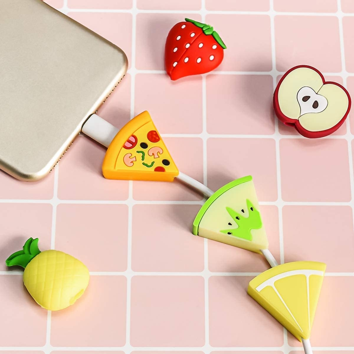a cellphone with a pizza, apple, and lemon cord charm