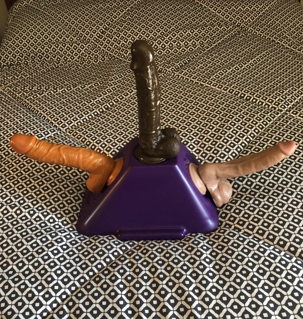 reviewer image of three dildos attached to two sides and the top of the TOM v2 suction dildo mount