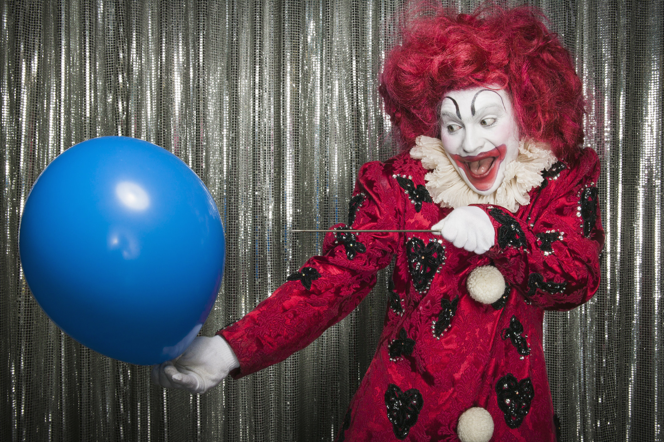 A clown pops a balloon with a needle.