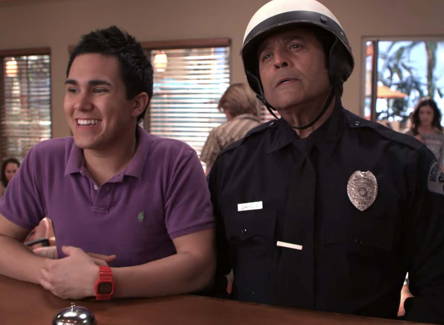 Erik Estrada wearing a police uniform and standing next to Carlos