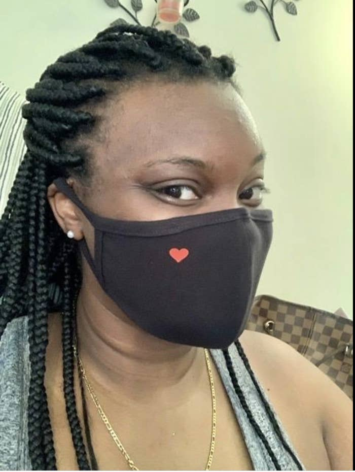 Reviewer in black face mask with subtle red heart on the right top side