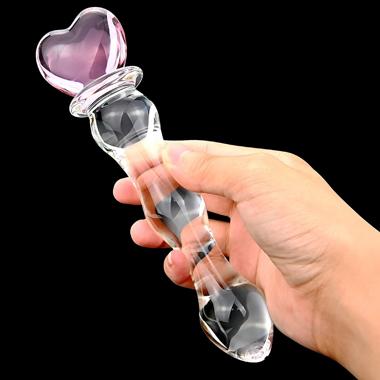 a model's hand holding the sex factory glass dildo up against a black background