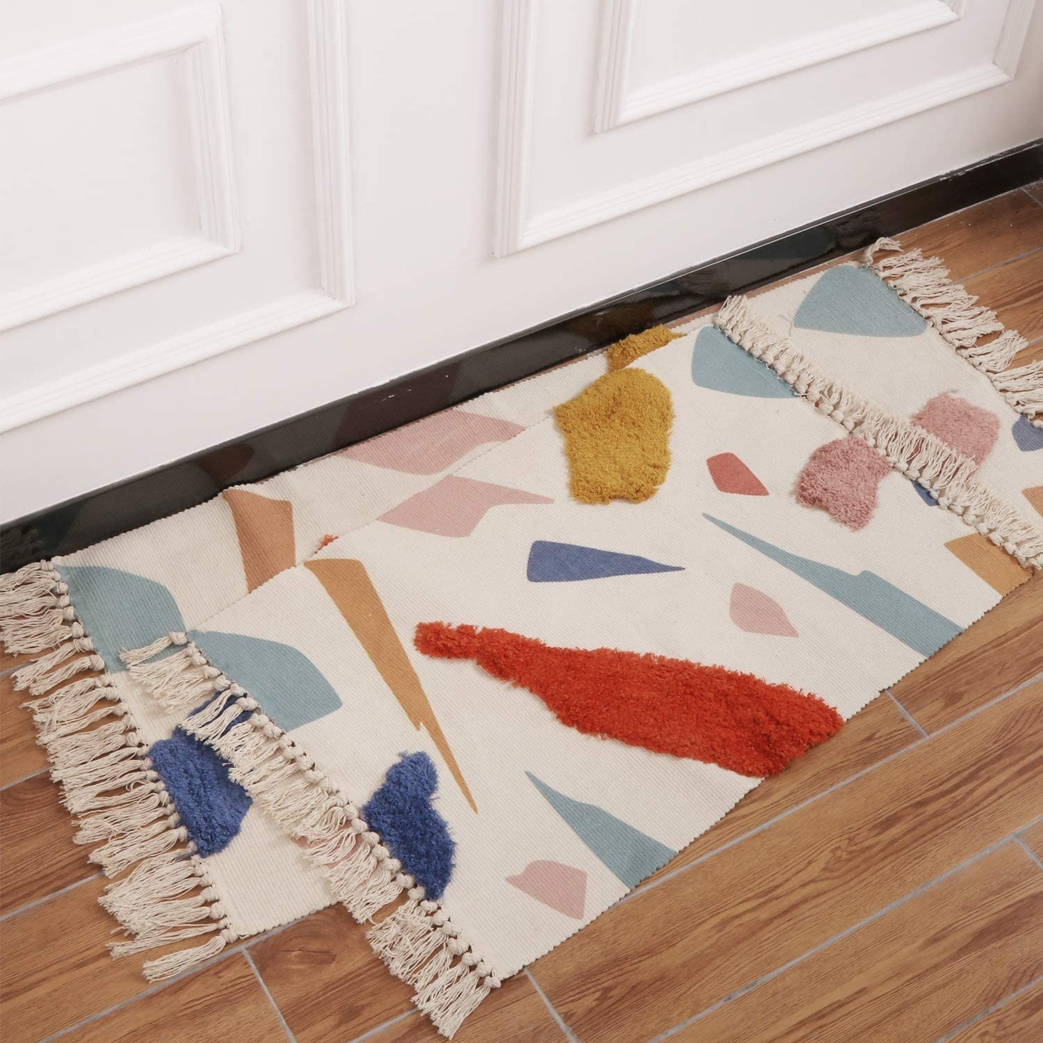Beige tasseled rugs on top of each other. Both have several different materials and colorful, geometric shapes