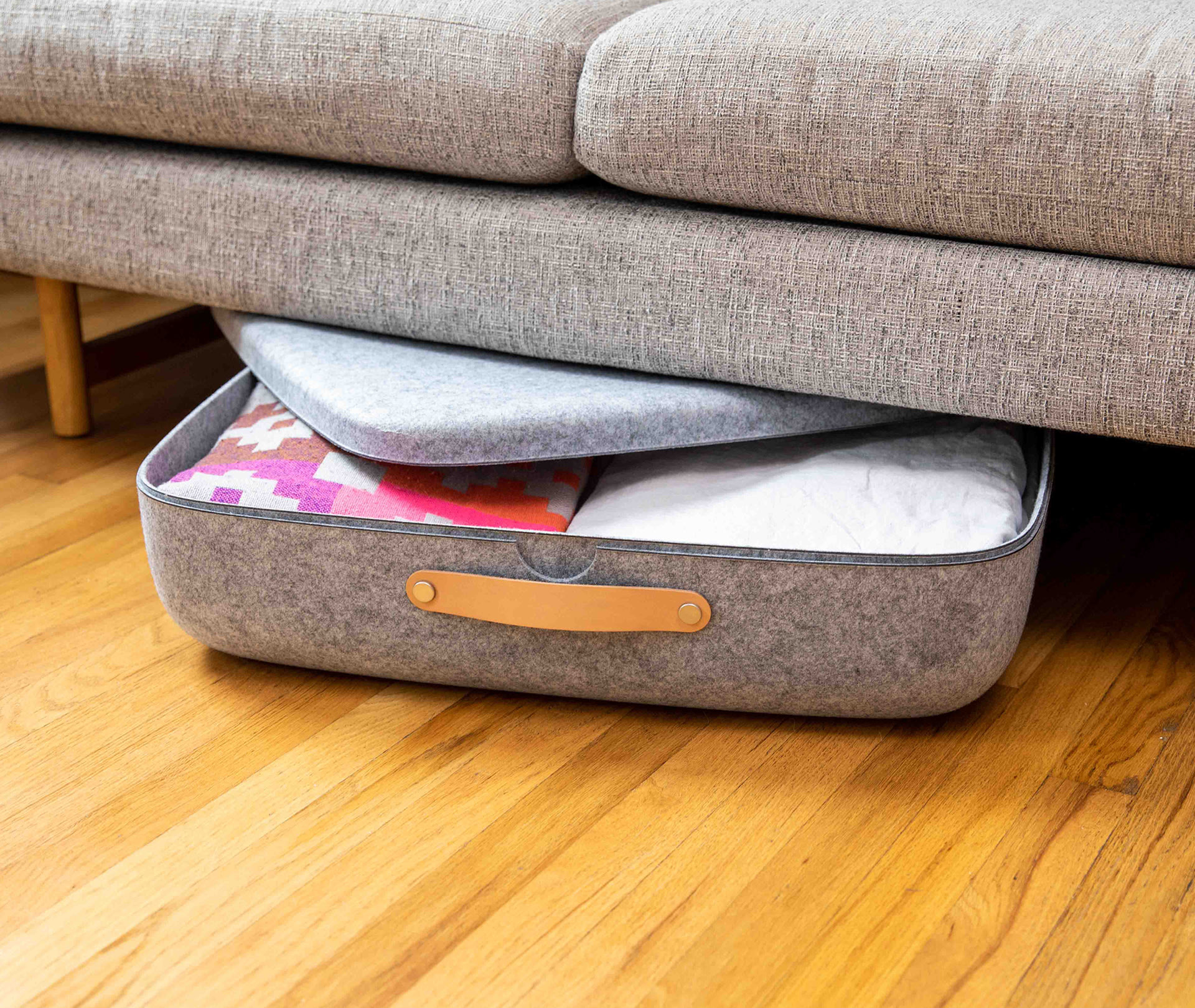 the square-shaped storage bin under a couch, with the lid off, showing how much can fit inside