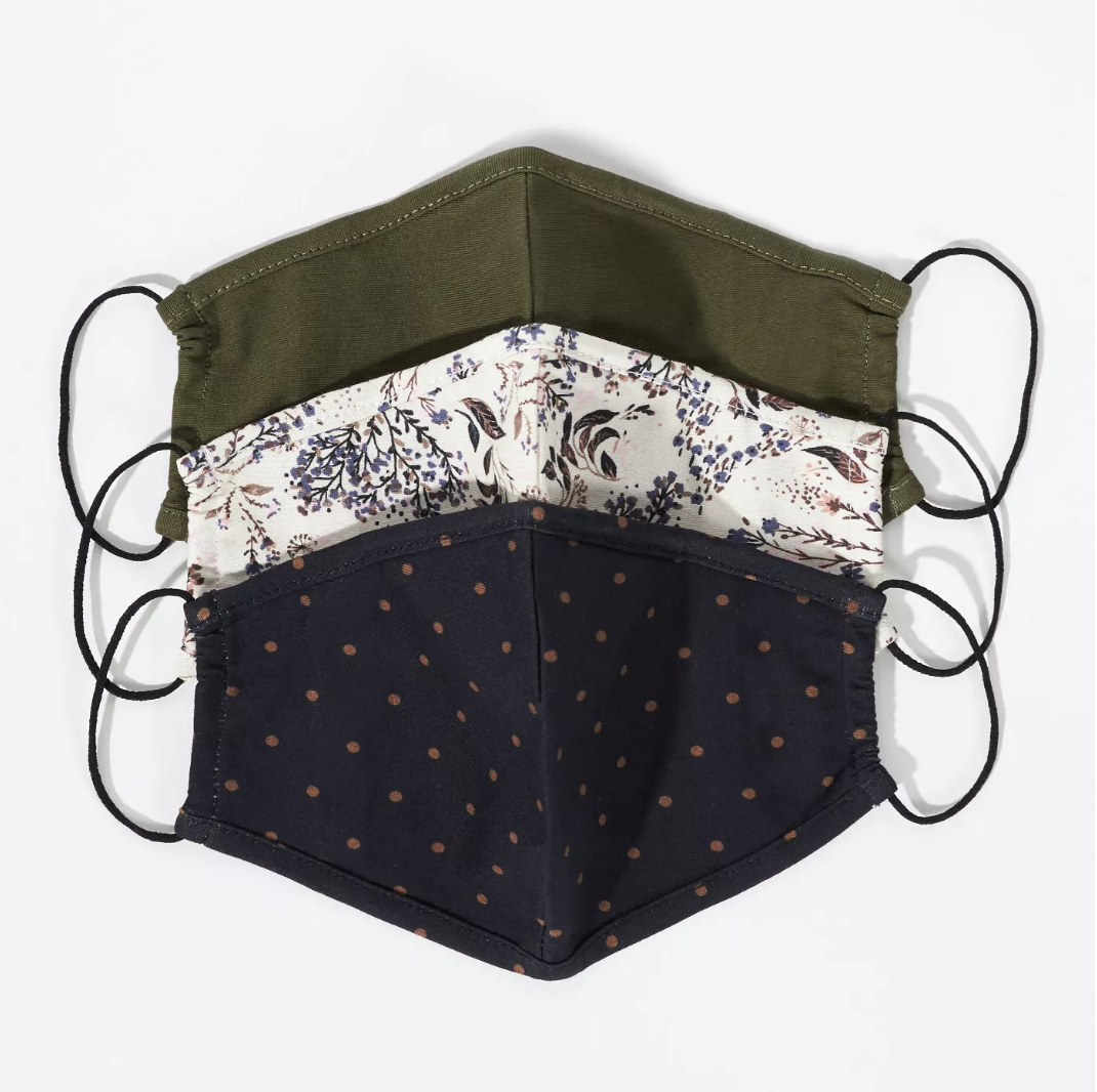 three masks, one in olive green, another in black with brown dots, another in white with dark blue and brown floral