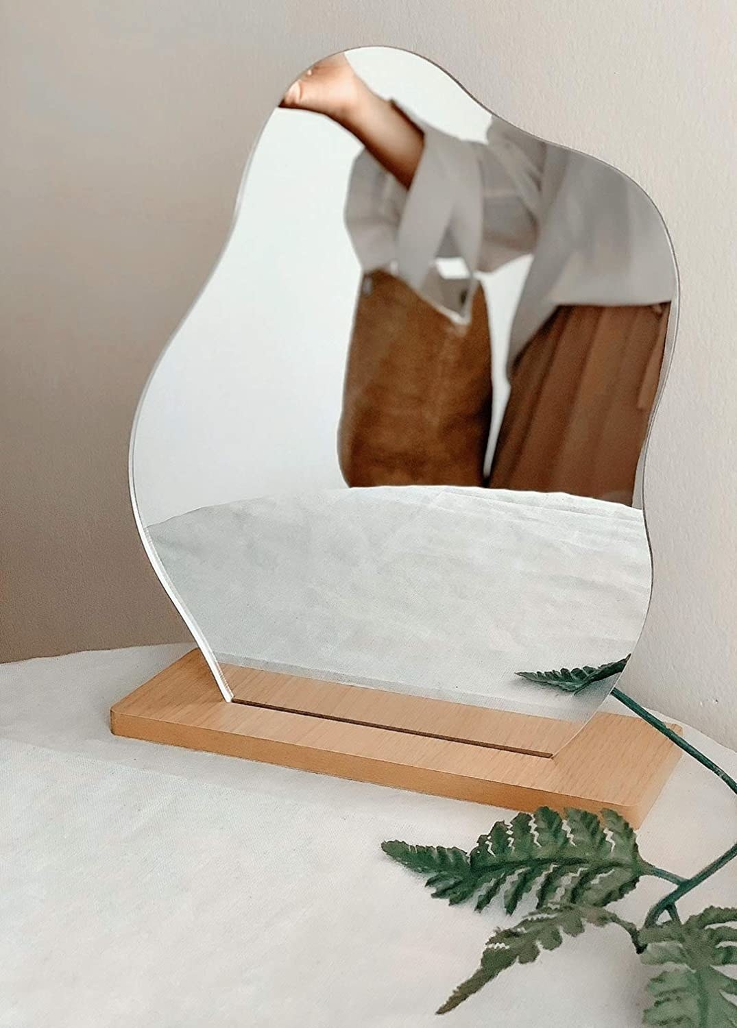 Curvy, small mirror on wooden base