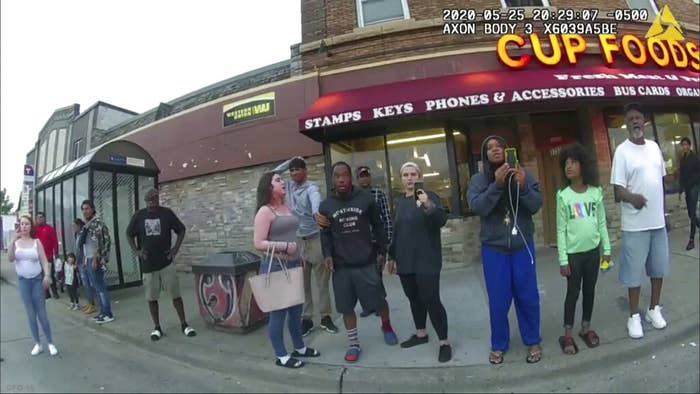 People standing on the sidewalk hold up cellphones in this still from a police body camera