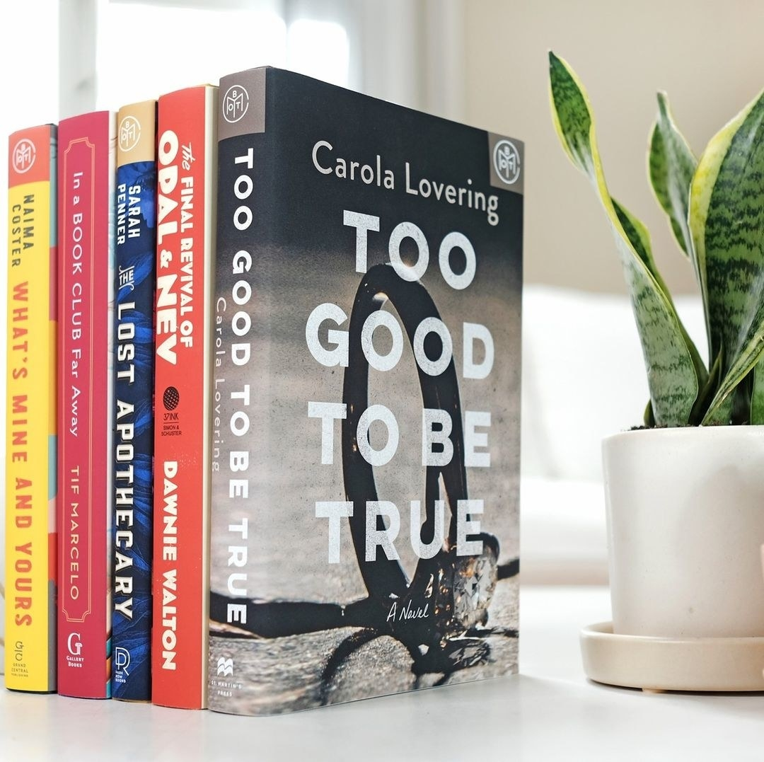five books stacked next to each other next to a plant