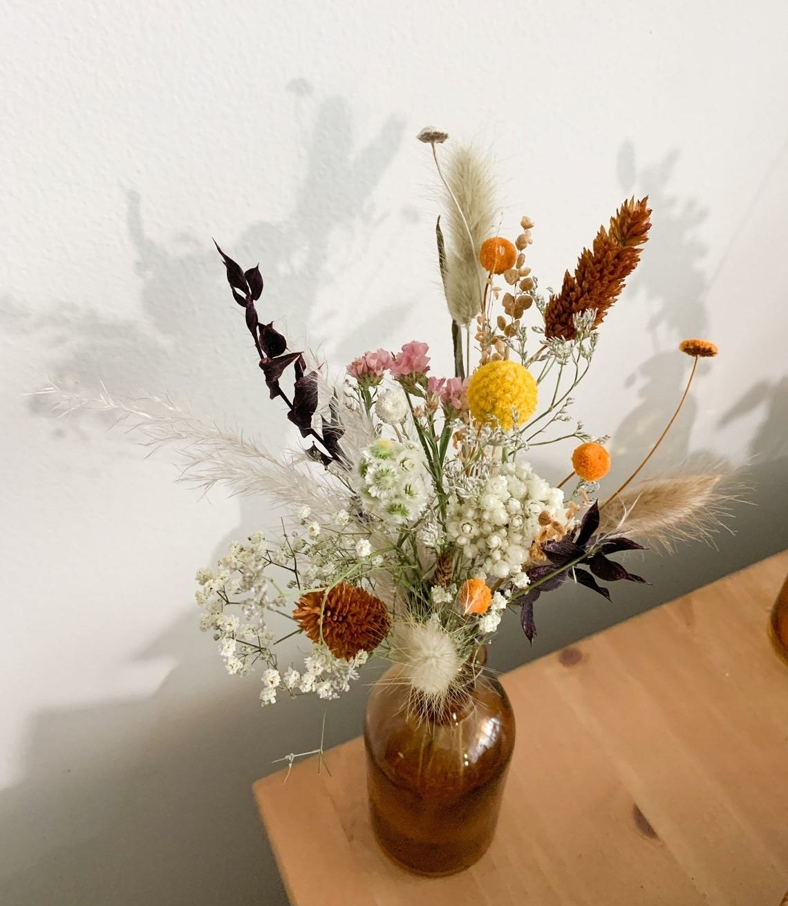 Several different stems of flowers arranged in an amber bottle