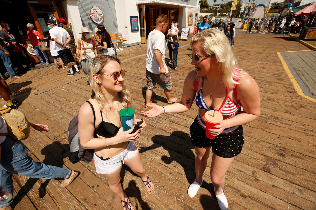 Two women talking on the boardwalk without masks