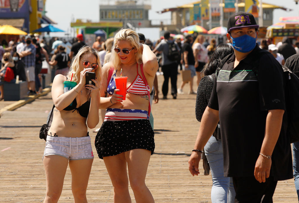 Two girls chatting without masks on the boardwalk