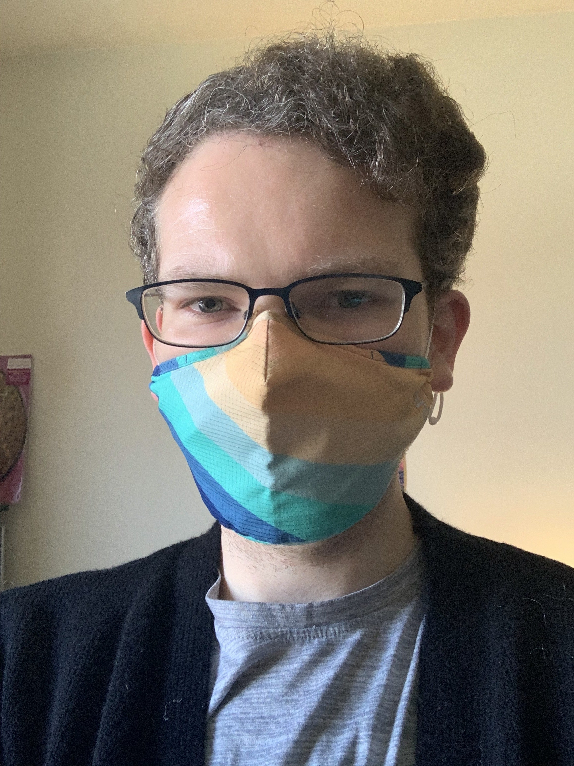 buzzfeed writer in a multicolored blue and yellow striped face mask