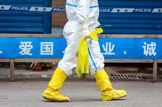 A person wearing full-body protective gear, including gloves and boots, carries a salamander in a plastic bag