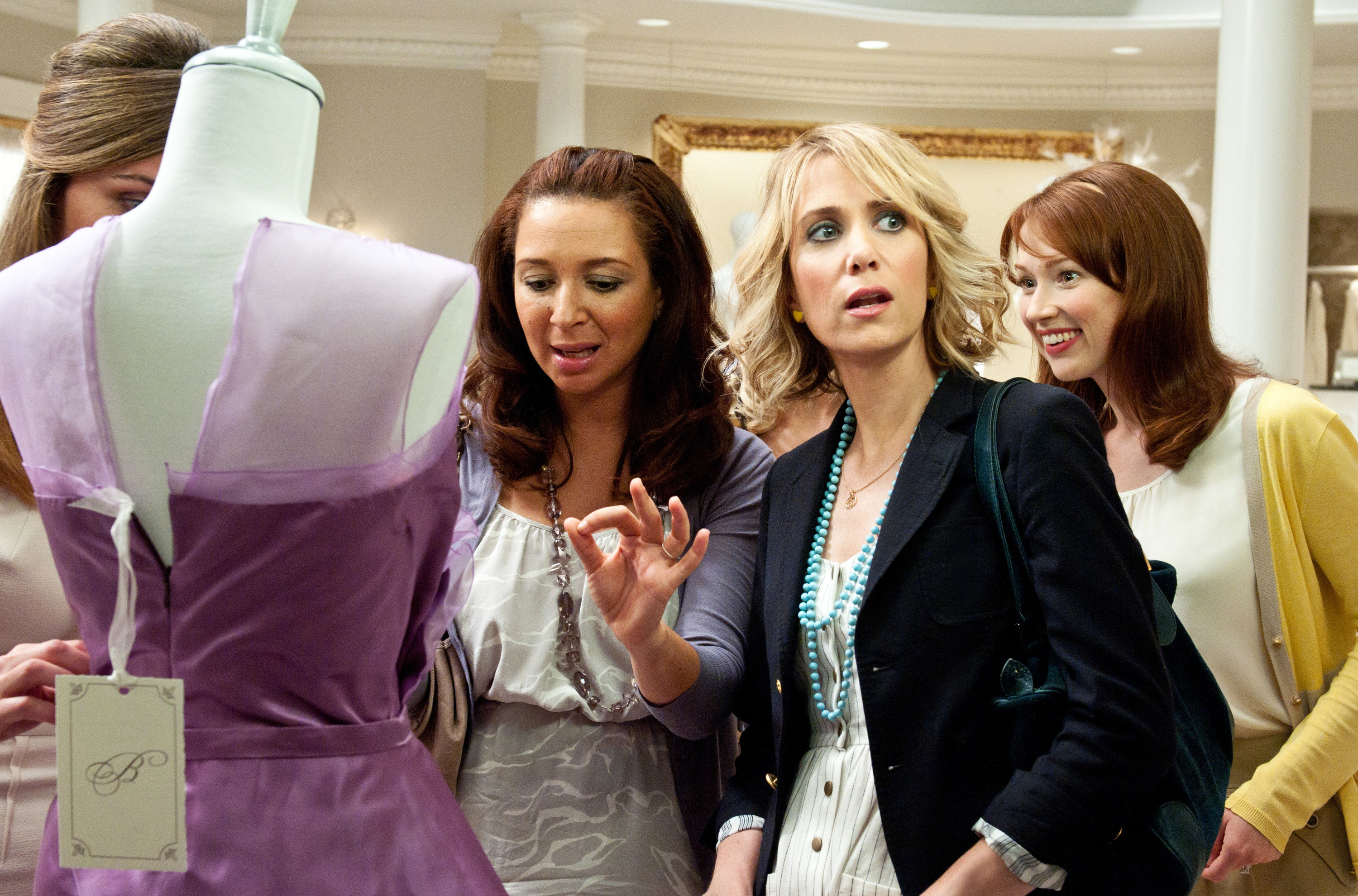 Rose Byrne (obscured by a mannequin), Maya Rudolph, Kristen Wiig, Ellie Kemper looking at a dress in a bridal store