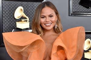 Chrissy wears a ruffled orange dress at an awards show last year