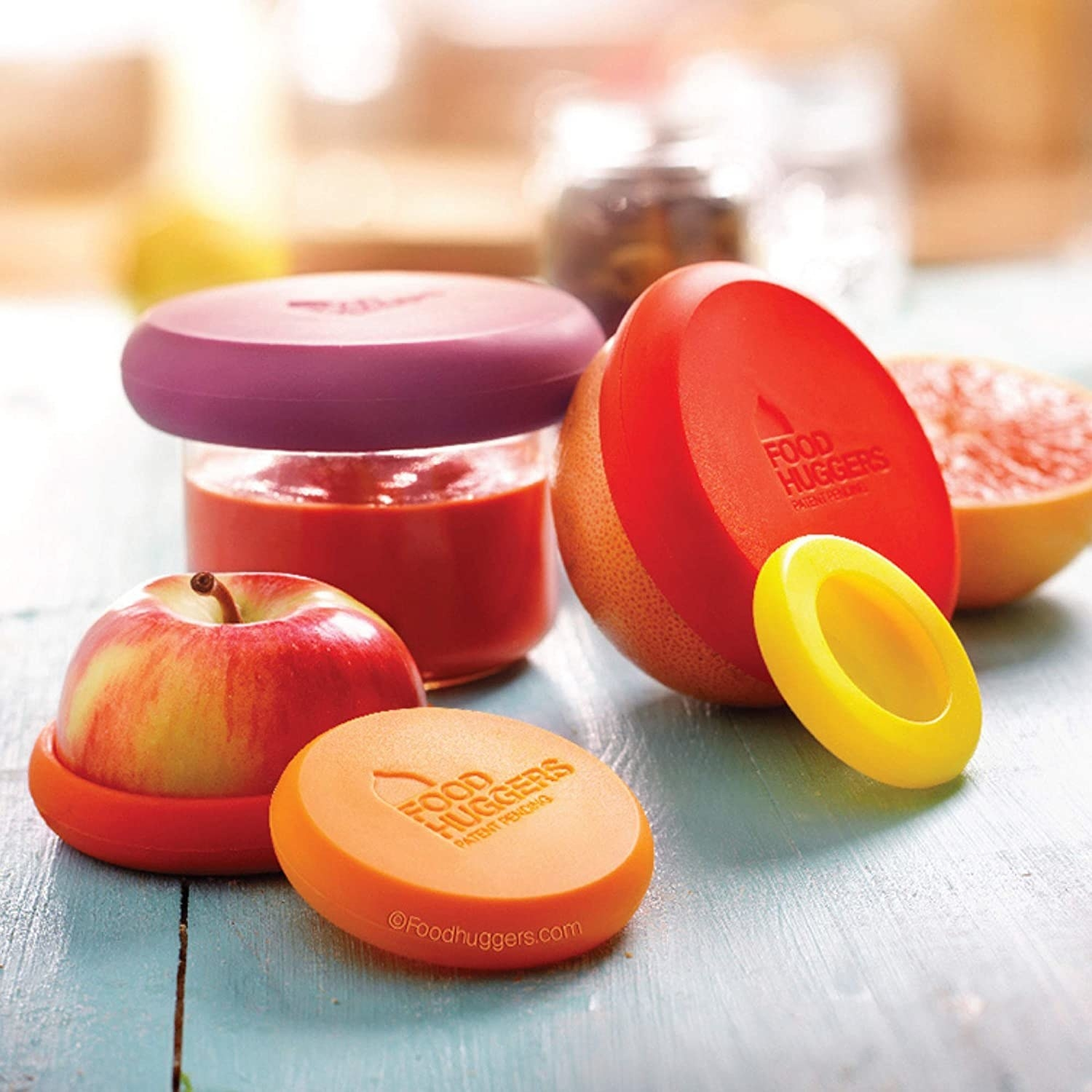 Five food huggers in shades of red and orange with one around a half an apple, one around an orange, and one on a cup of sauce