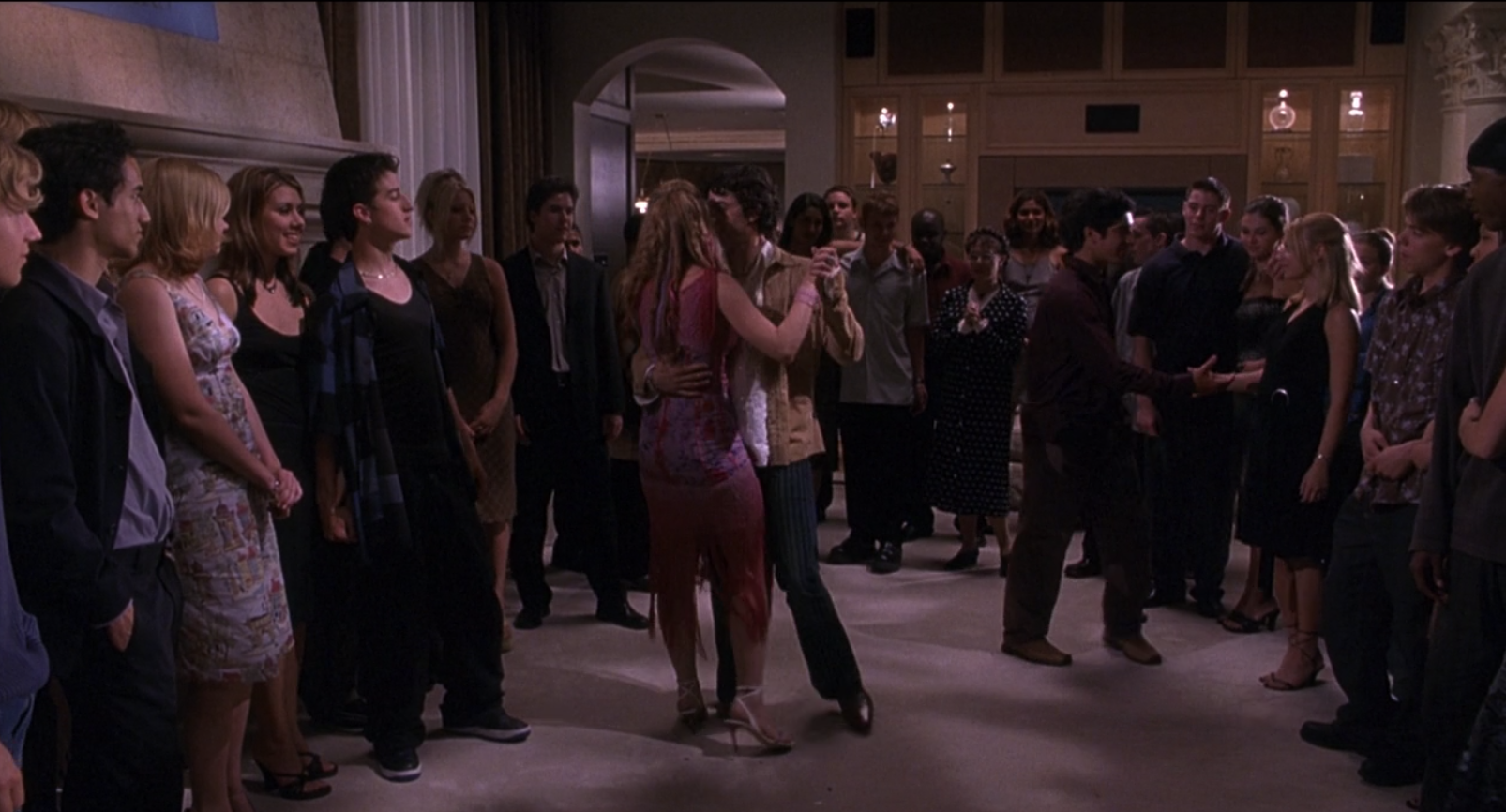 Lola and Stu Wolf slow dancing in the room of a teen party