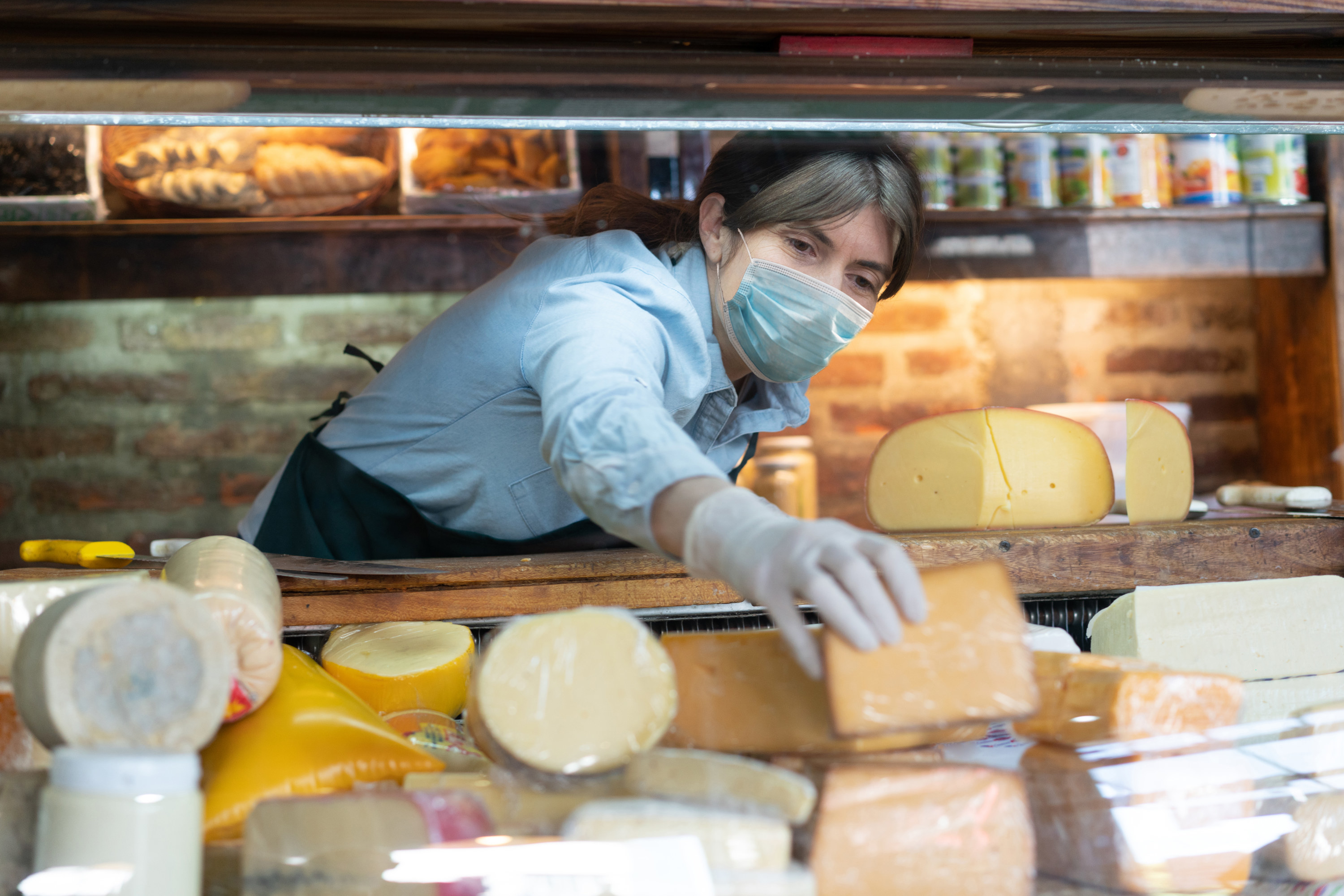 Deli worker rearranging cheese