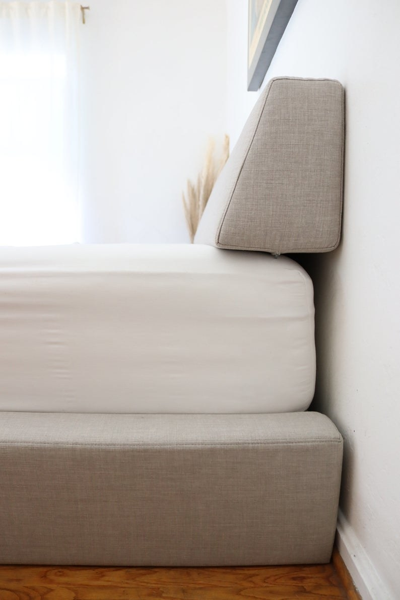 side view of bolster pillow on bed up against a wall