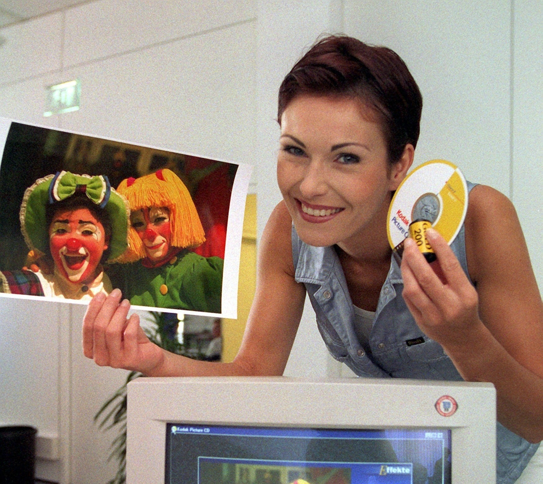 A woman holding a large photo of two female clowns in one hand and a photo CD and film in the other