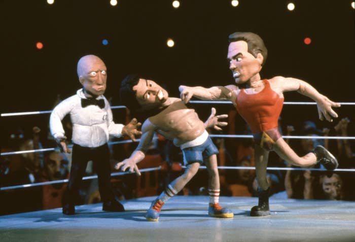 A photo of claymation versions of Sylvester Stallone being punched by Arnold Schwarzenegger in a boxing ring