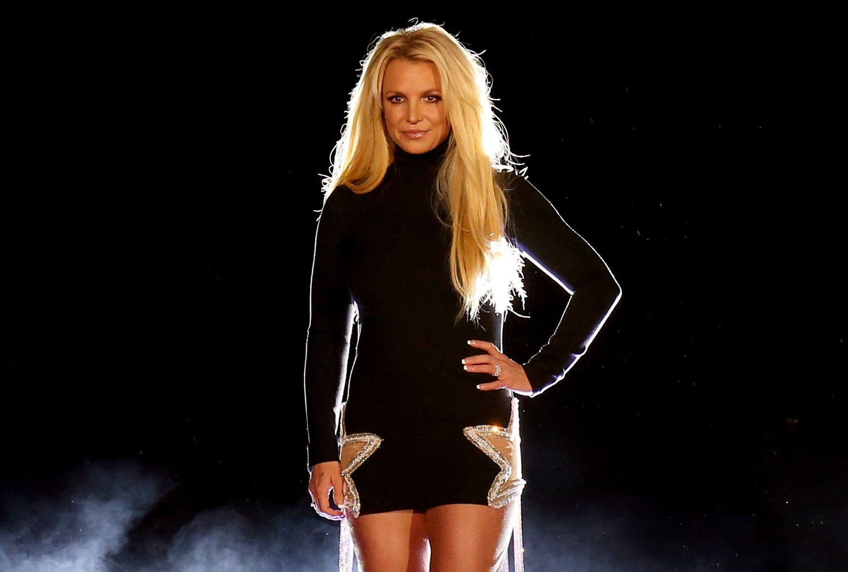 Britney poses with her hand on her hip while on stage at an event