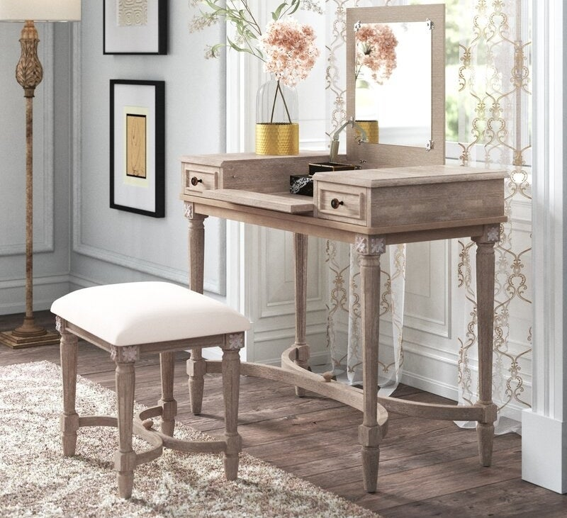 Wooden vanity with a curved, decorative vase and matching stool