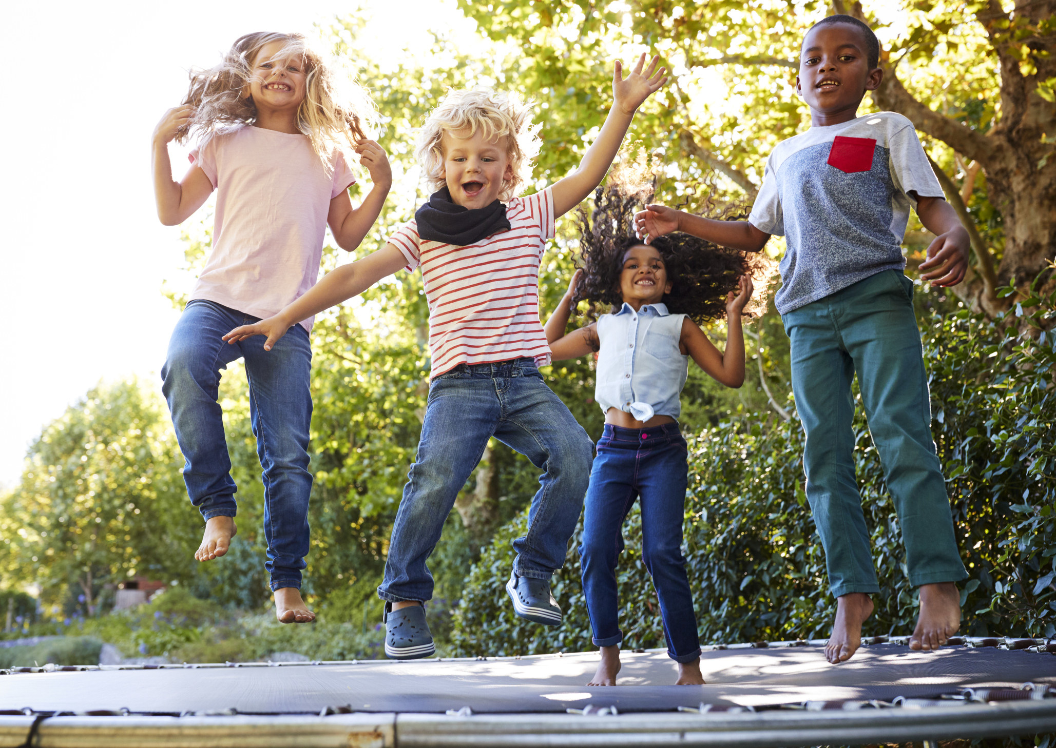 Four kids jumping on a trampoline