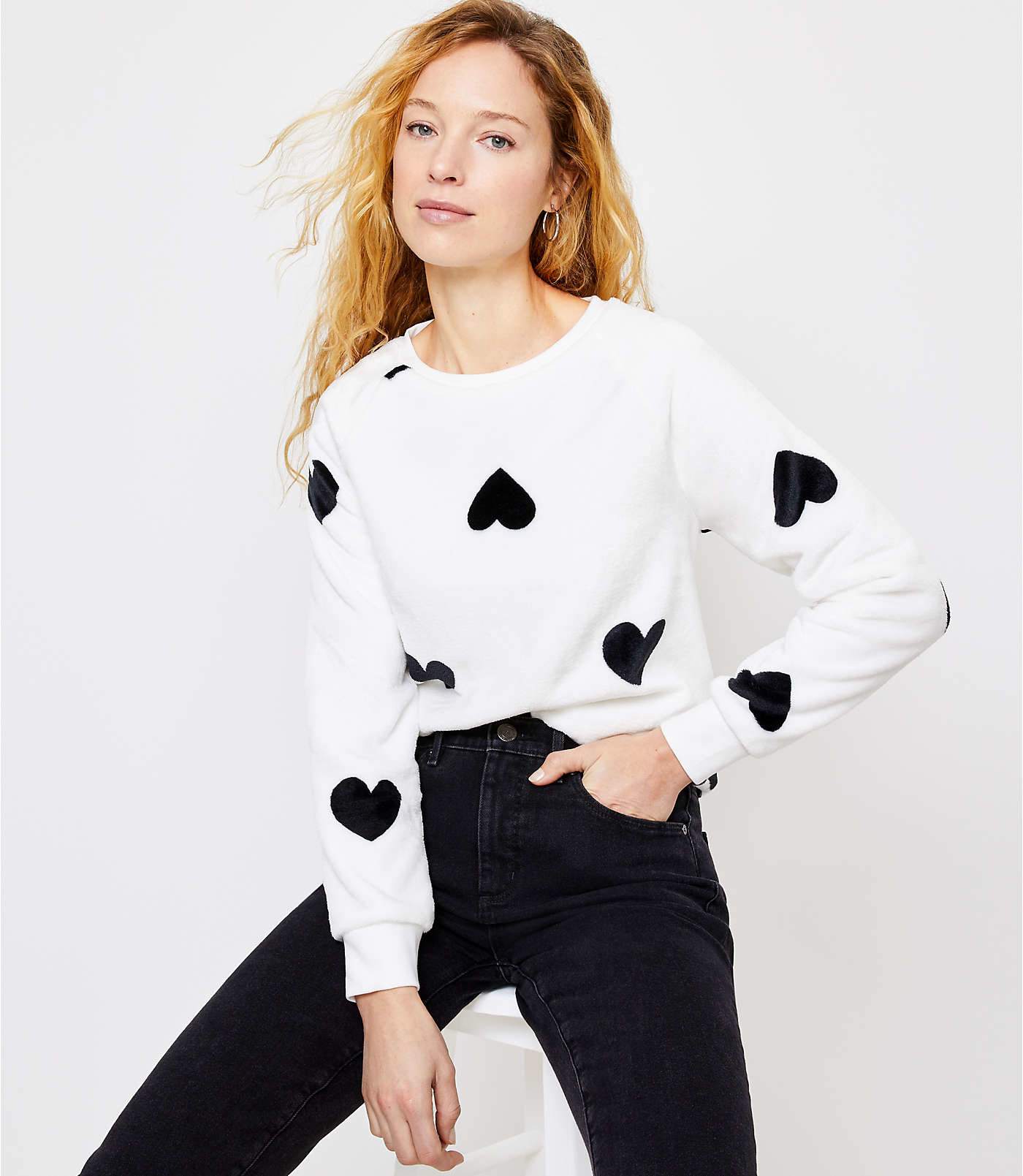 Model wearing the white sweatshirt with black novelty print hearts