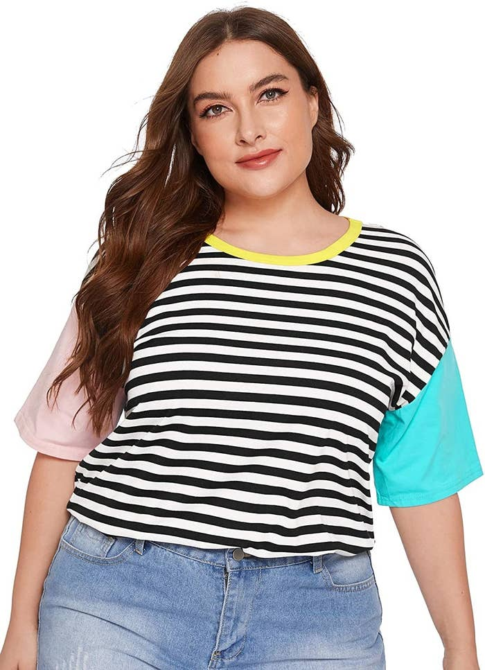 Model wearing black and white striped tee with pink and blue sleeves