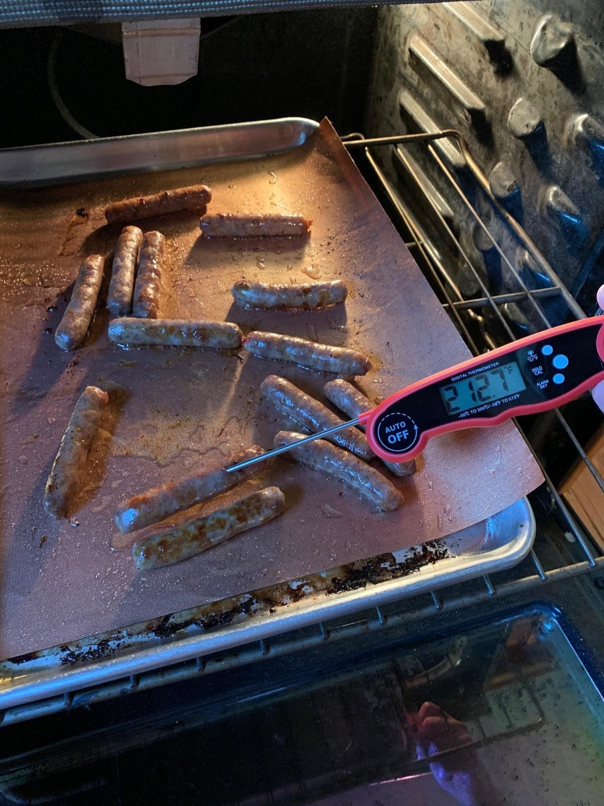 image of reviewer using the red meat thermometer to check the temperature of oven-baked sausages