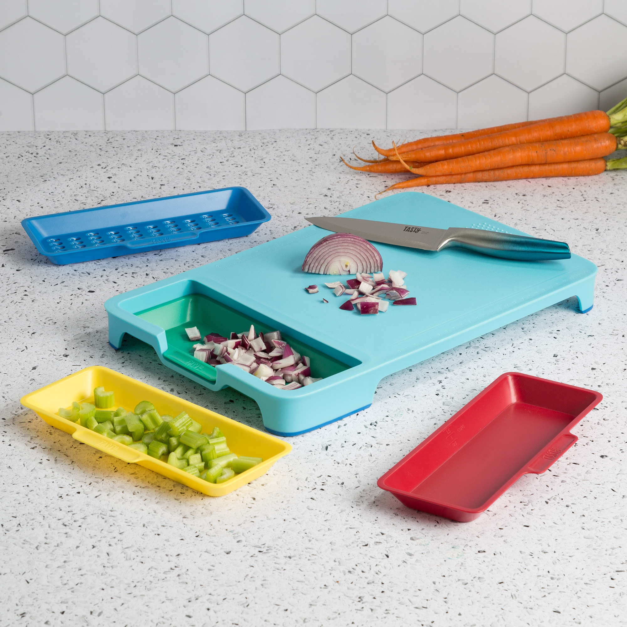 the blue cutting board with diced onion on it and in the green tray, and the blue, red, and yellow trays, with one holding celery, next to it on a counter