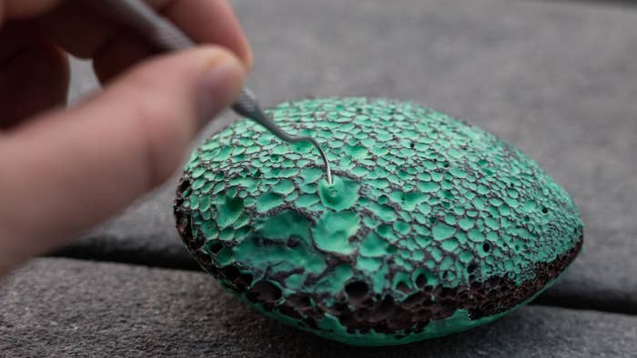 A model using a tiny hook to pick blue paint out of a lava rock with tiny holes