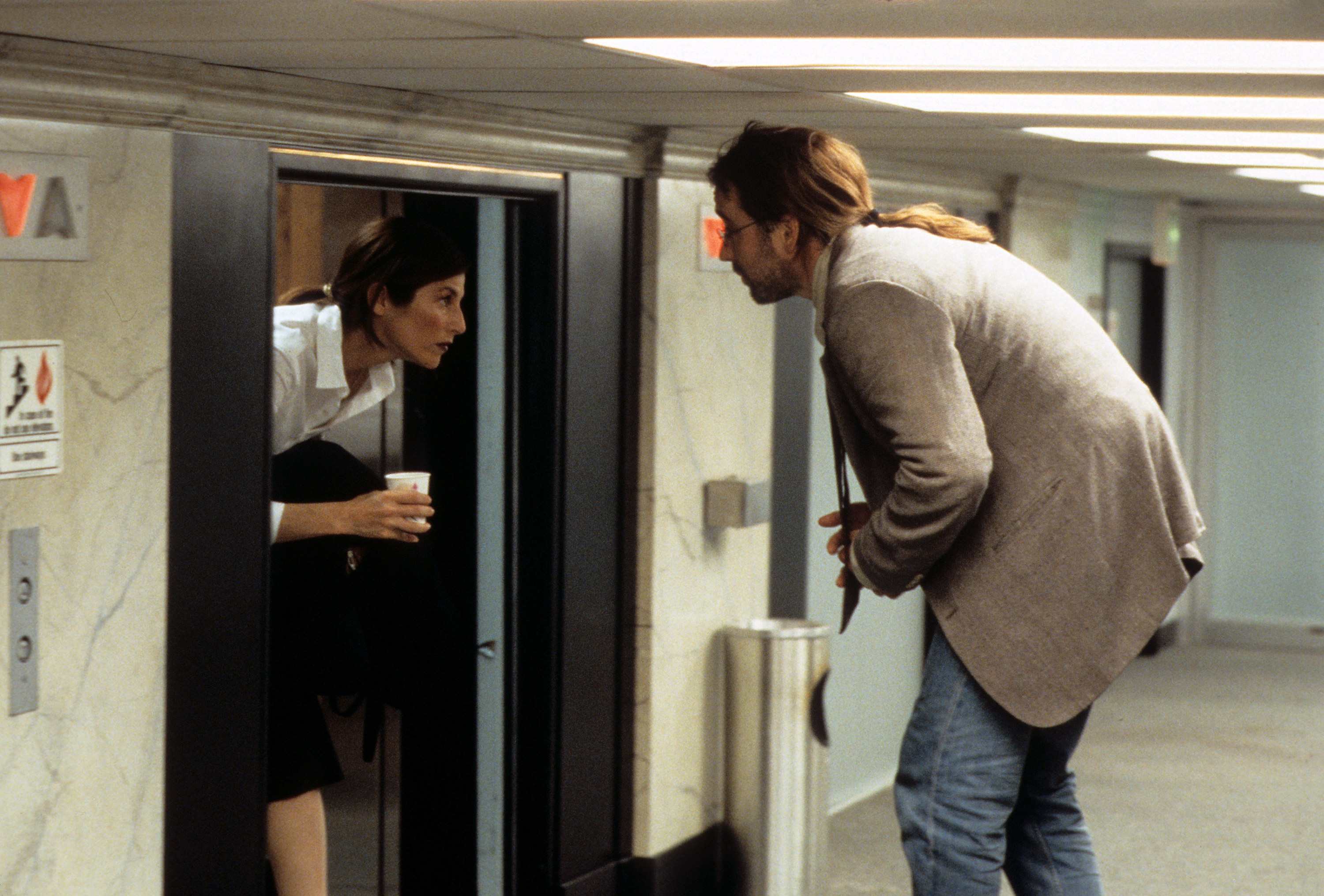 Two people looking at each other as one exits a tiny elevator