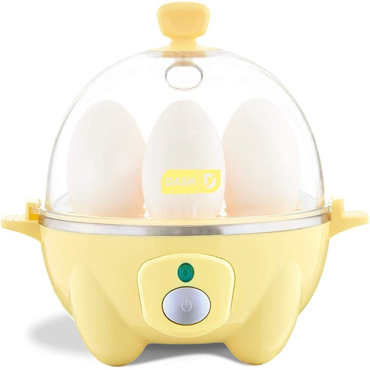 The egg cooker in pastel yellow, filled with eggs. It has a clear dome top and handles at the top and sides