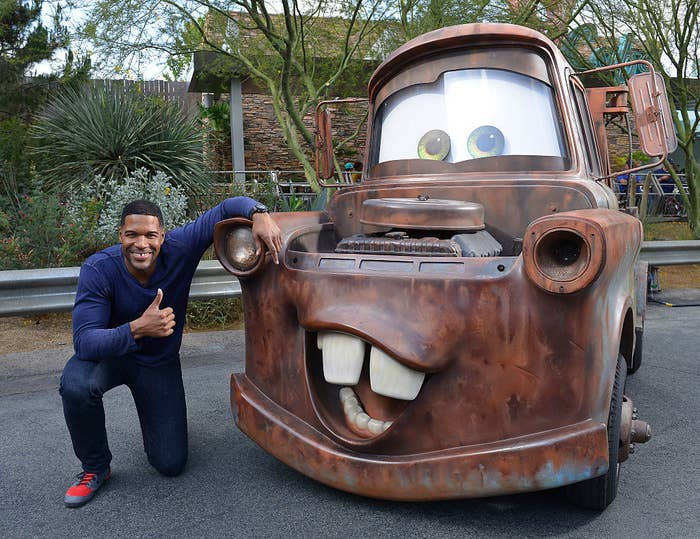 Michael smiling and posing with Cars movie character Tow Mater