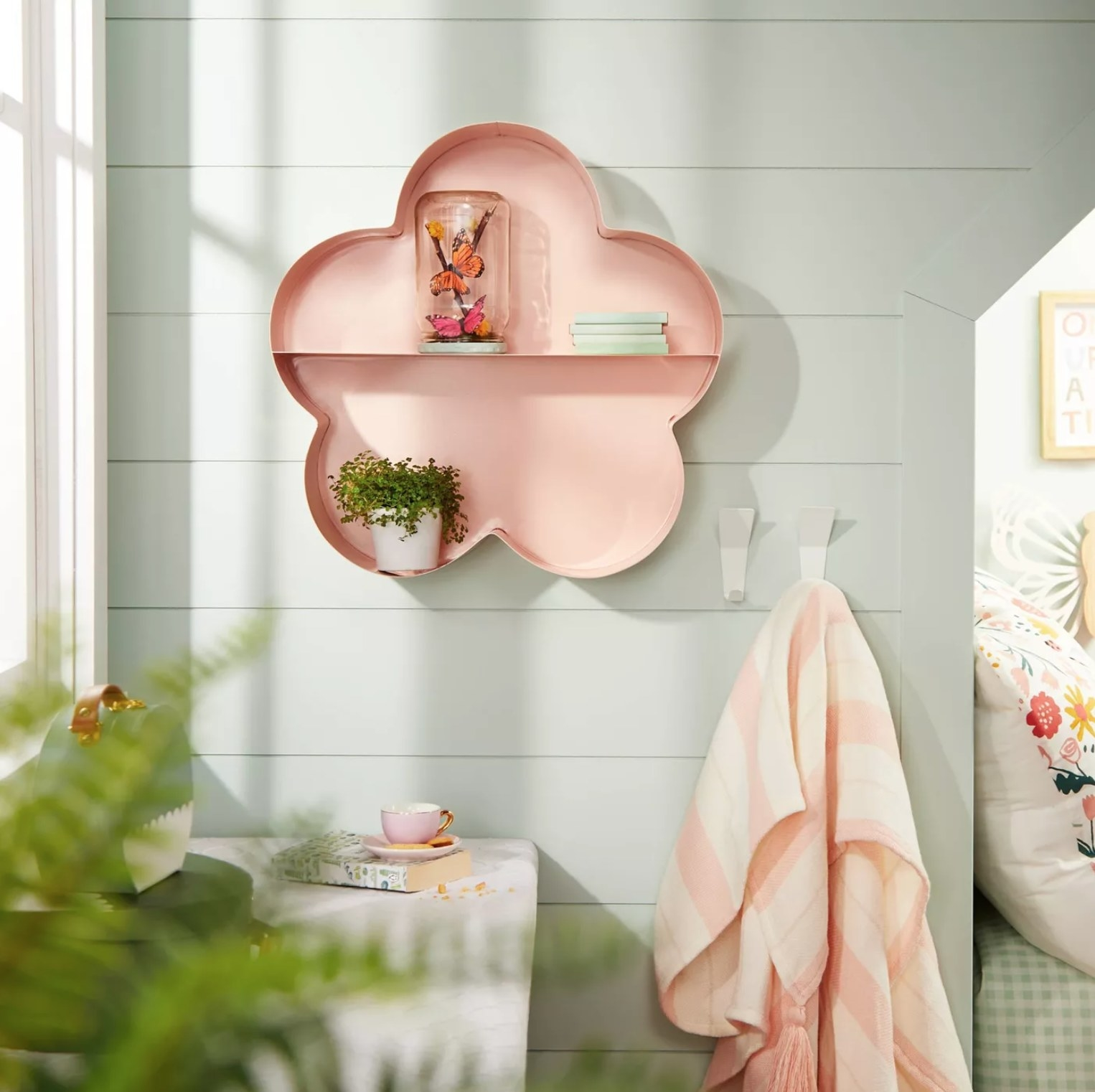 The pink shelf on a wall with a plant and other decorations
