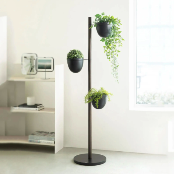 A tiered plant stand with three planters