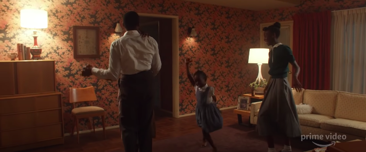 A Black family dances in their living room.
