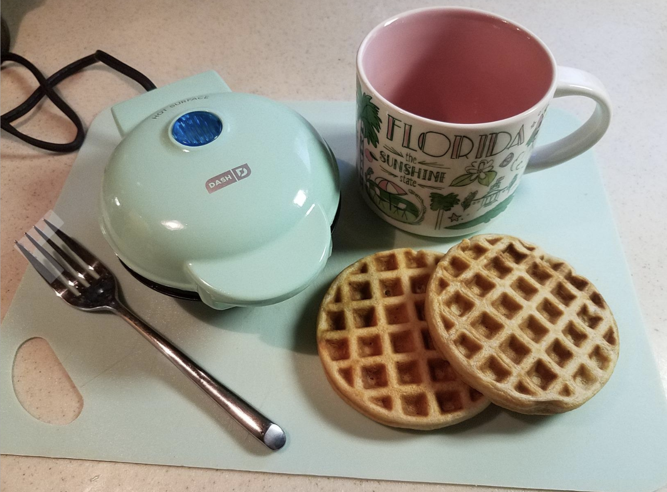 two cooked waffles next to small blue waffle maker