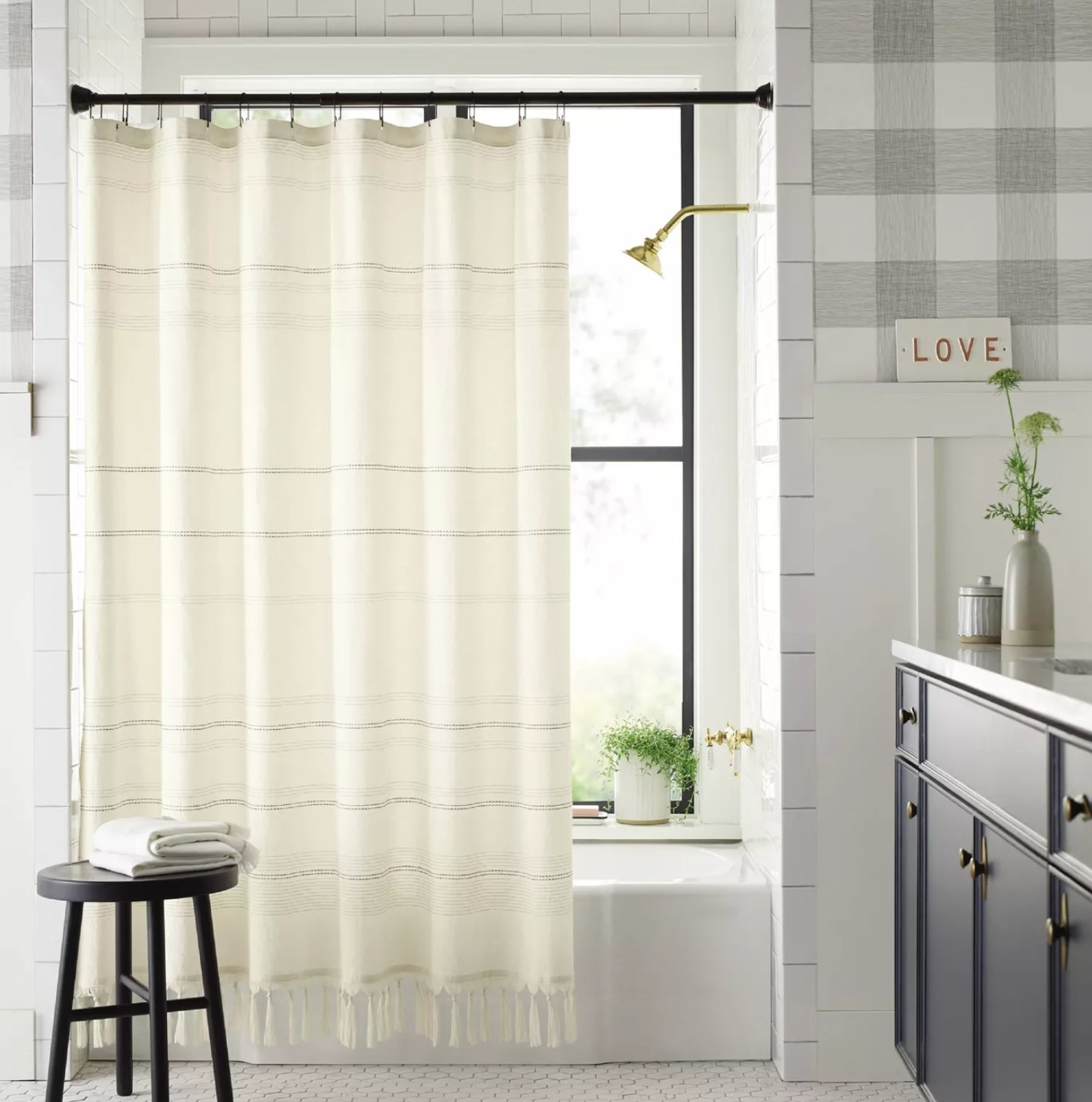 The curtain in a bathroom hanging on a shower rod