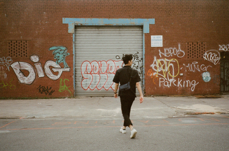A man walks towards a wall with grafitti