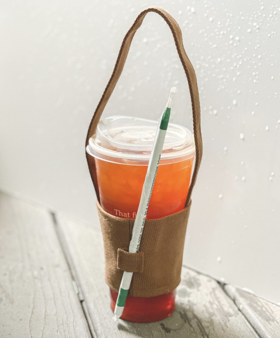 An iced drink in a coffee cup holder with a straw