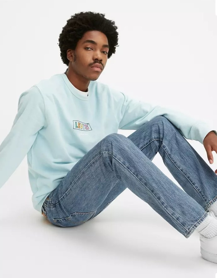 Model wearing classic straight-fit blue jeans with light blue shirt