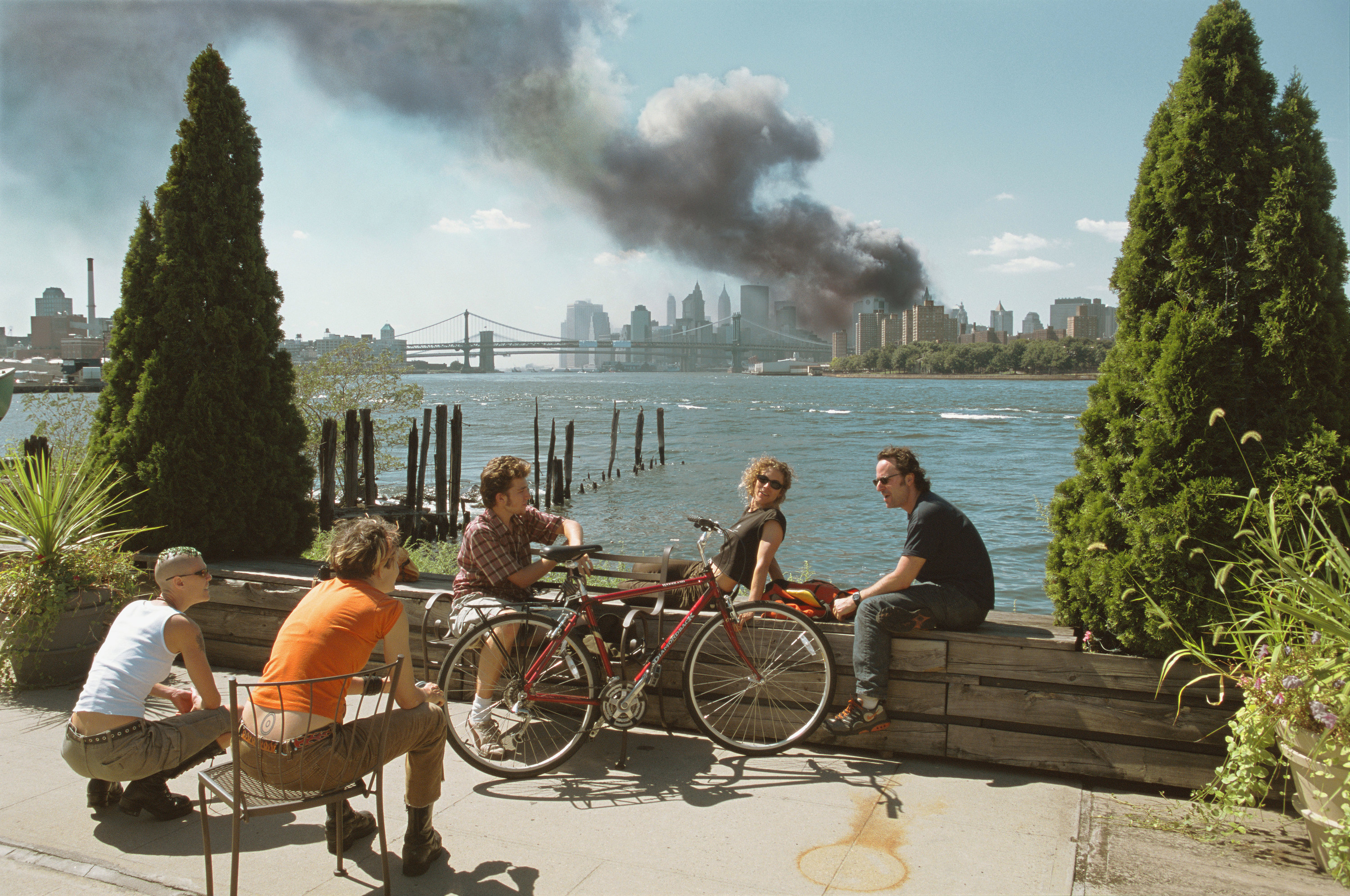 Young people relax during their lunch break along the East River while a huge plume of smoke rises from Lower Manhattan after the attack on the World Trade Center