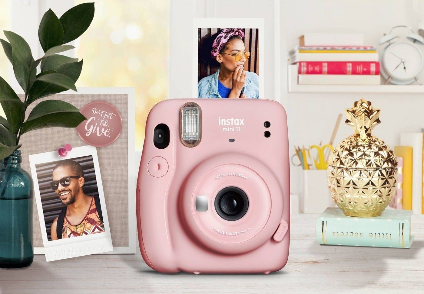 pink instant camera on a desk that's printing out a picture